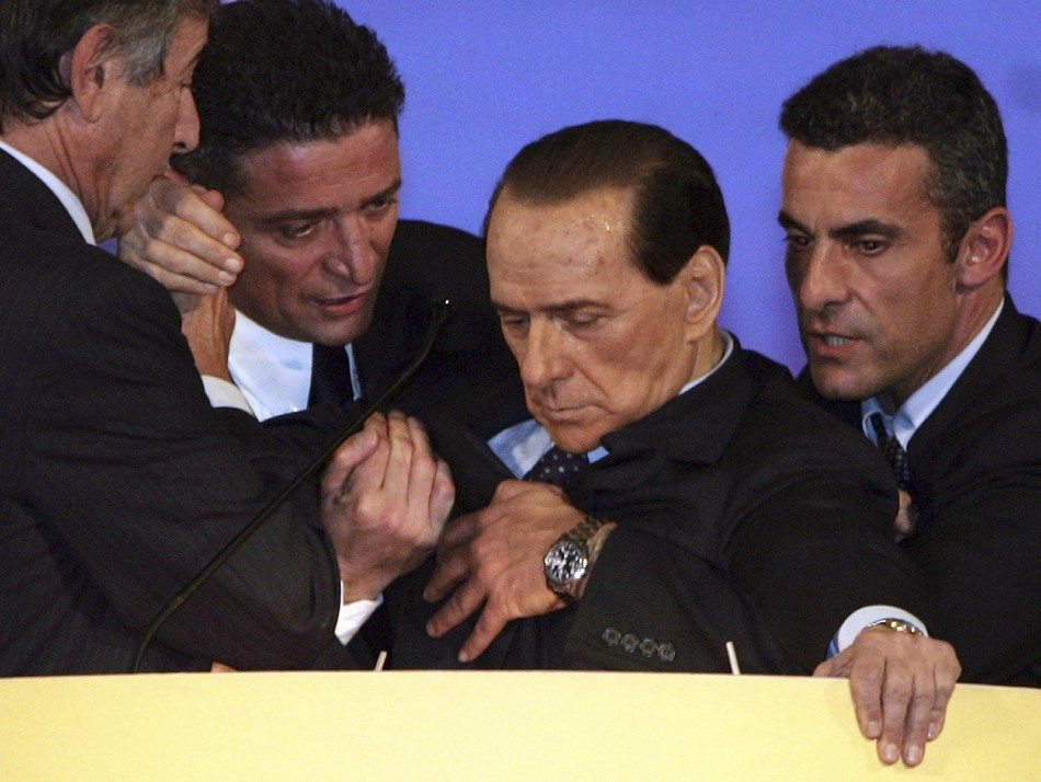 Silvio Berlusconi is assisted by aides after collapsing in Tuscany