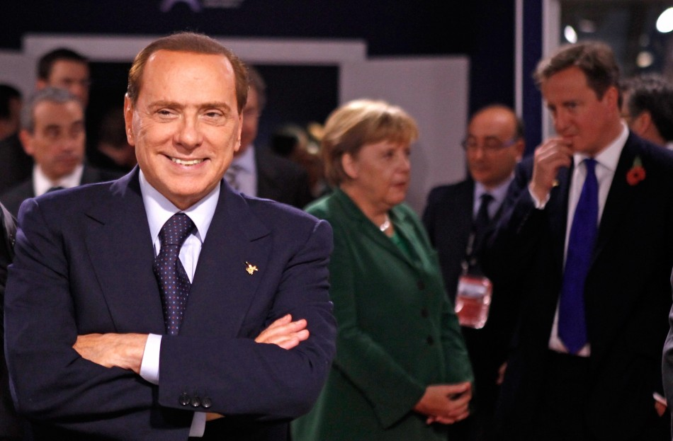 Italy's PM Berlusconi looks on as Germany's Chancellor Merkel and Britain's PM Cameron talk during the G20 summit in Cannes