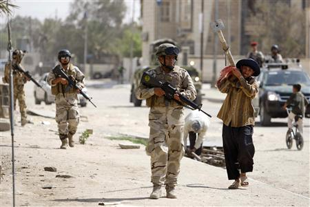 Soldiers patrol along a street during a security operation in Basra