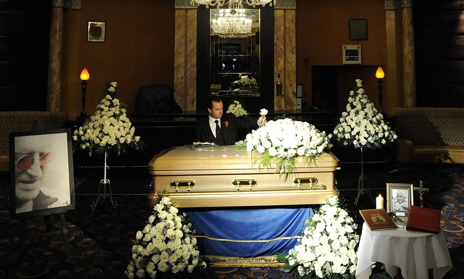 Funeral director Robert Morphet stands by the coffin of British entertainer Jimmy Saville, as it is displayed to the public at The Queens Hotel in Leeds