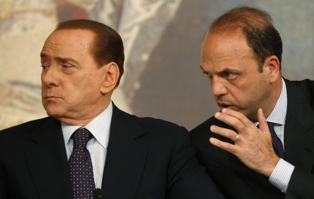 Italian Justice Minister Alfano talks with Prime Minister Berlusconi during a news conference in Rome