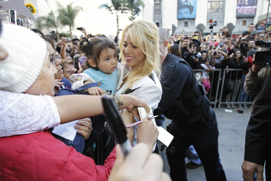 Colombian singer Shakira (C) carries a baby while greeting her fans after she unveiled her star on the Hollywood Walk of Fame in Hollywood, California November 8, 2011