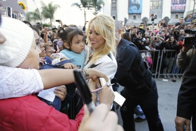 Colombian singer Shakira C carries a baby while greeting her fans after she unveiled her star on the Hollywood Walk of Fame in Hollywood, California November 8, 2011