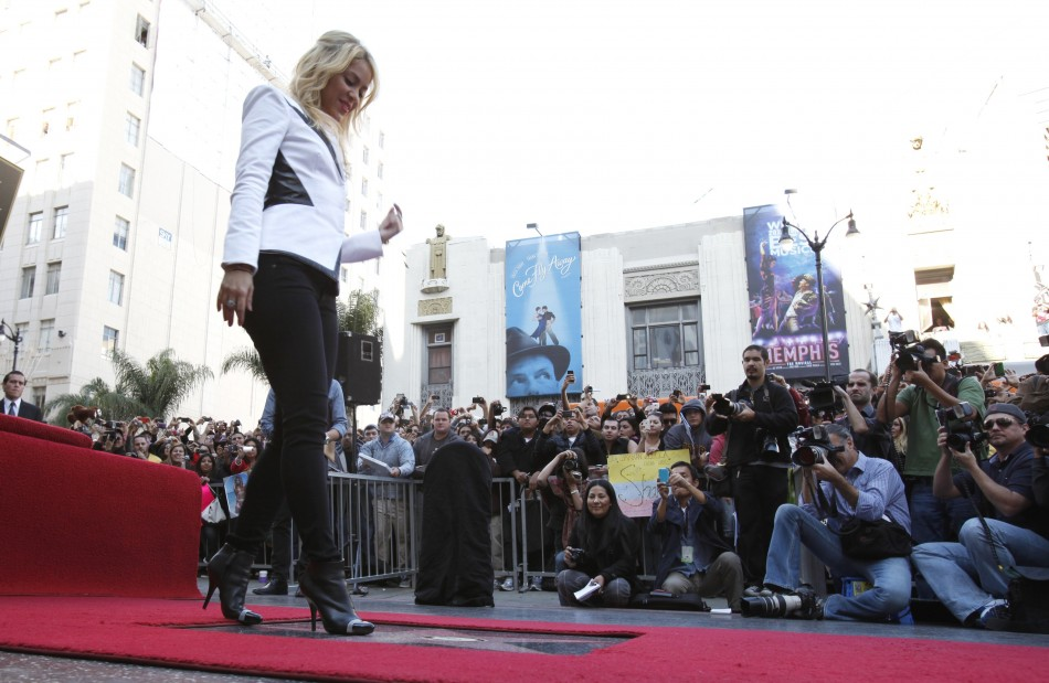 Shakira poses on her star after it was unveiled on the Hollywood Walk of Fame in Hollywood, California November 8, 2011.