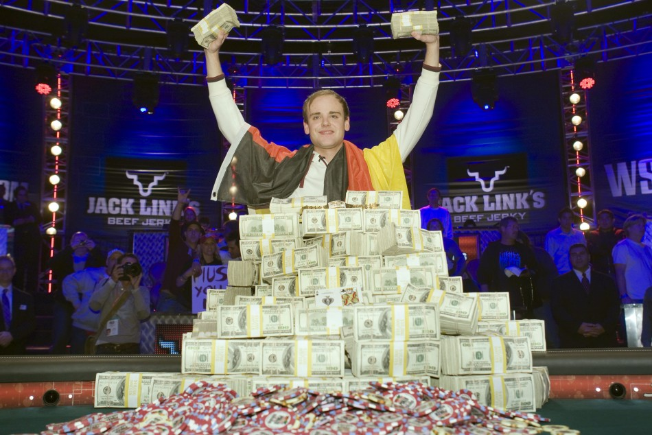 Pius Heinz of Germany poses with stacks of cash after beating Martin Staszko of the Czech Republic to win the championship bracelet and $8.7 million in prize money during the World Series of Poker main event at the Rio hotel-casino in Las Vegas