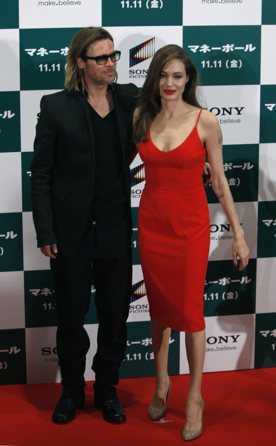 "U.S. actor Brad Pitt and his partner Angelina Jolie pose during the Japan premiere of Pitt's film ""Moneyball"" in Tokyo"