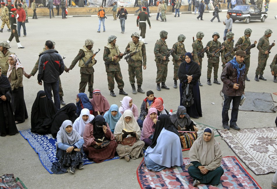 Women opposition supporters sit in front of Egyptian soldiers at Tahrir Square in Cairo
