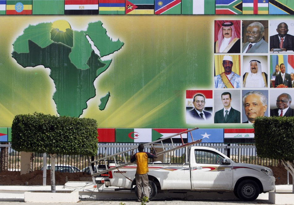 An organizer carries a ladder under a banner showing the African continent in Sirte