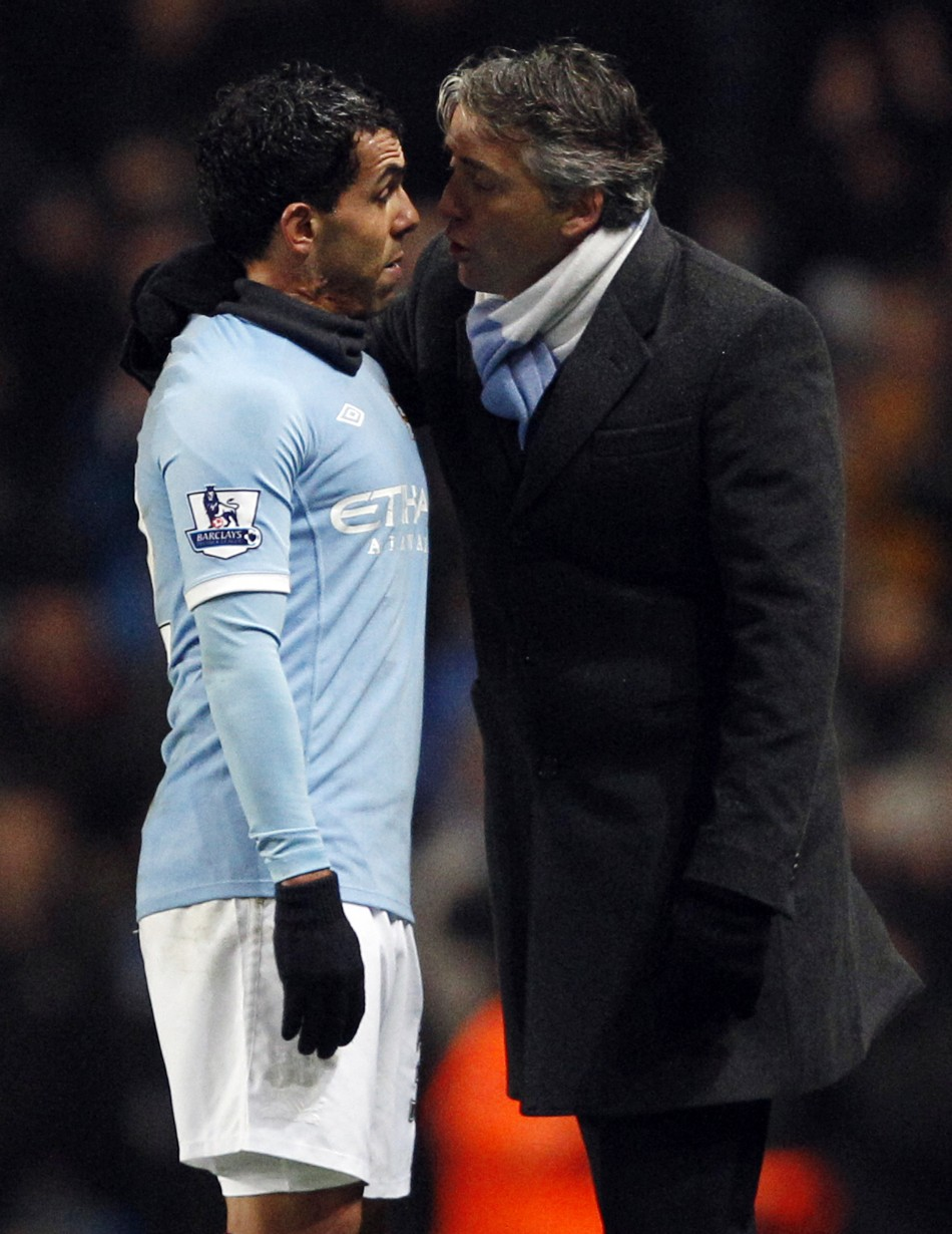 Manchester City's Tevez argues with manager Mancini after being substituted during their English Premier League soccer match against Bolton Wanderers in Manchester