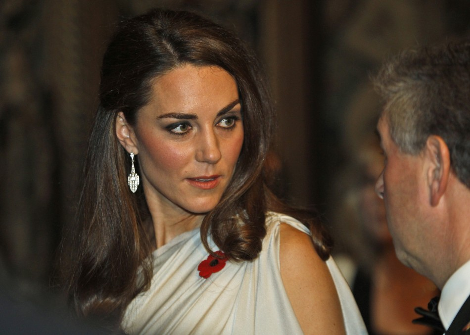 Kate looks dashing as she listens to a guest