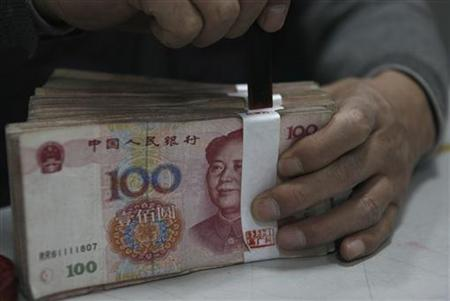 An employee seals a stack of yuan banknotes