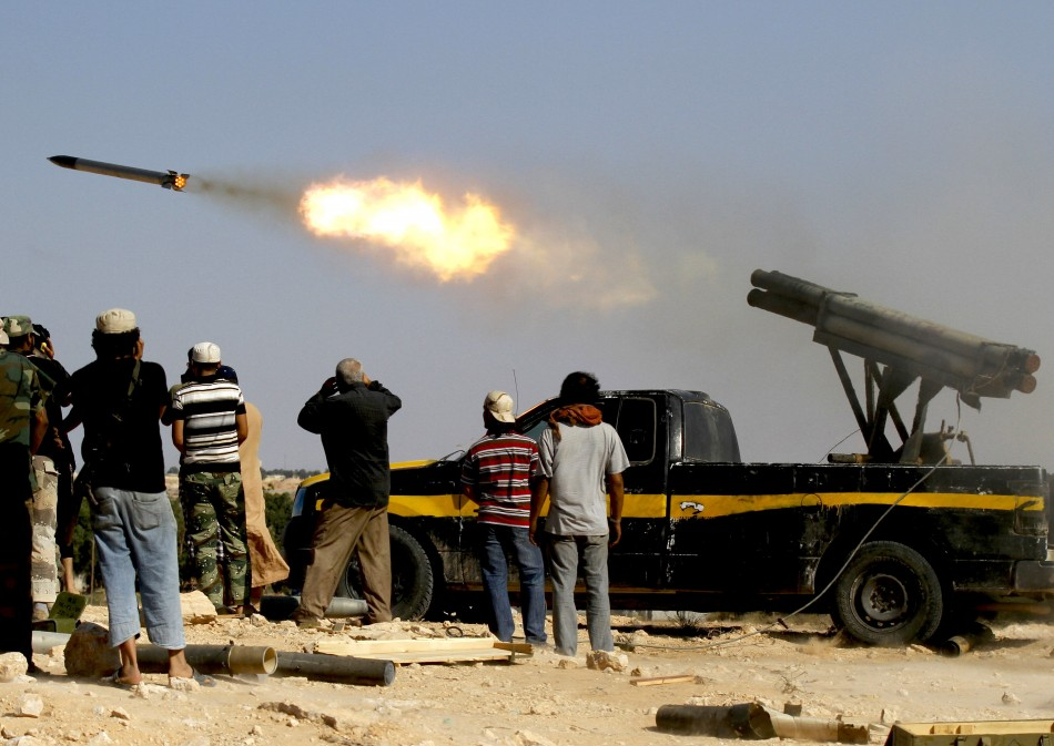 Forces loyal to Libya's interim rulers fire rockets at an area in Libya