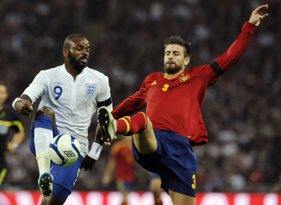 England's Bent is challenged by Spain's Pique during their international friendly soccer match in London