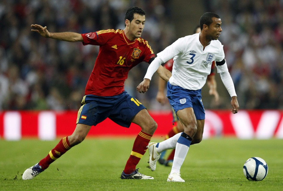 England's Cole and Spain's Busquets challenge for the ball during their international friendly soccer match at Wembley Stadium in London