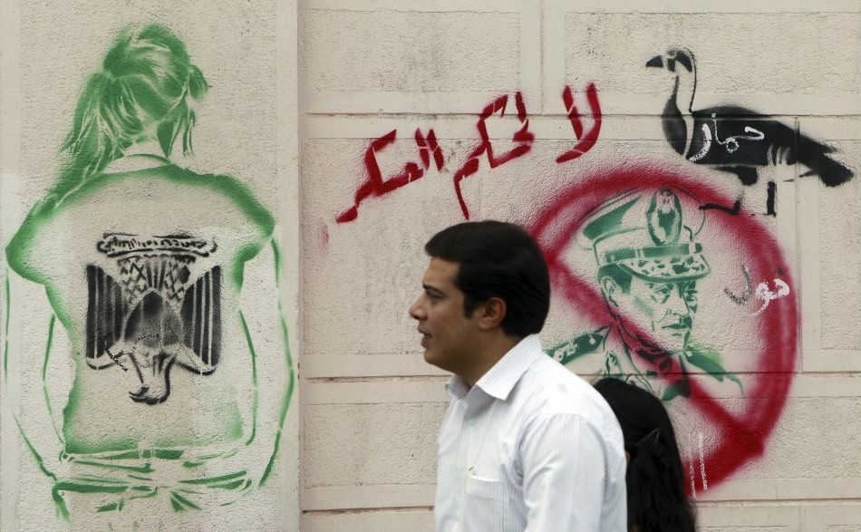 """An Egyptian man walks past a graffiti of past a graffiti of former Egyptian President Hosni Mubarak and writing """"Who is Protecting the Tyrant"""" at downtown in Cairo"""