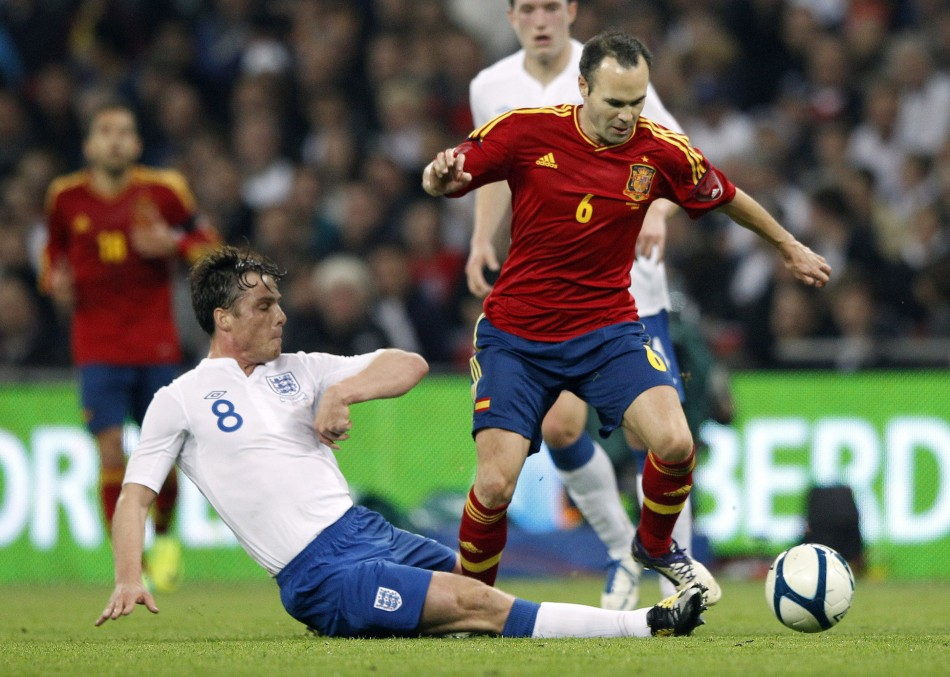 Spain's Iniesta is tackled by England's Parker during their international friendly soccer match at Wembley Stadium in London