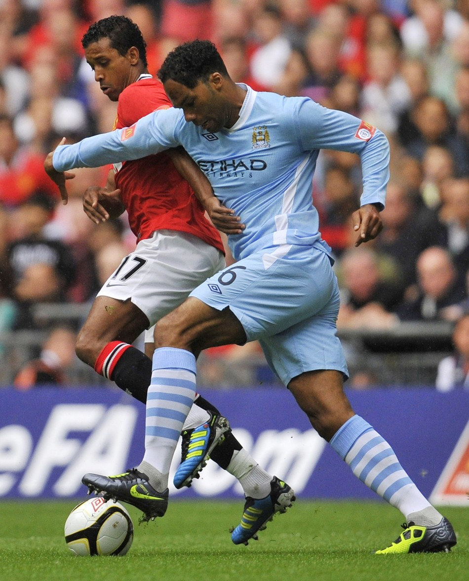 Manchester United's Nani is challenged by Manchester City's Joleon Lescott during their FA Community Shield soccer match at Wembley Stadium in London