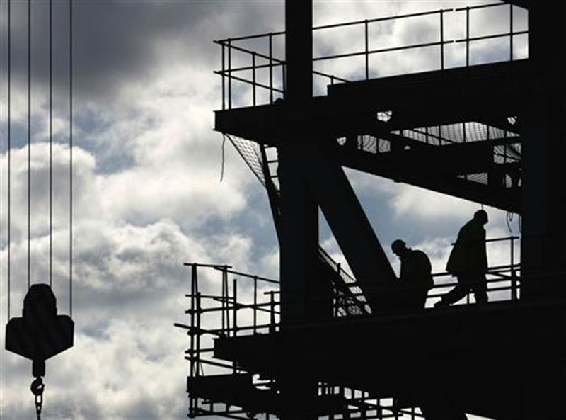 Workers are silhouetted on a construction site in London