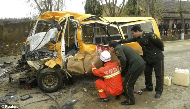 Rescuers inspect a school bus after it collided with a truck killing 18 children