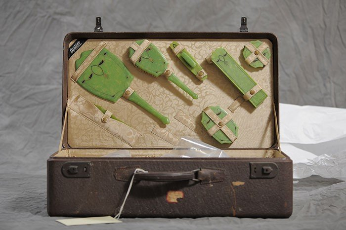 Suitcase containing green hairbrushes