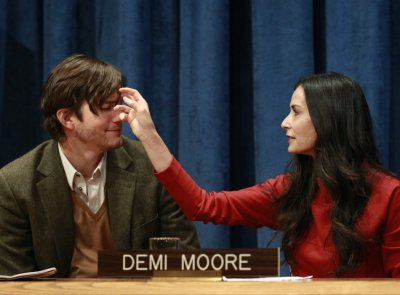 Actress Demi Moore brushes her husband, Ashton Kutchers hair, prior to a news conference at the United Nations Headquarters in New York