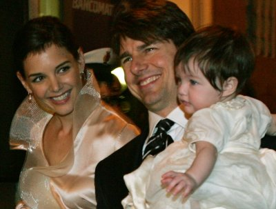 Actor Tom Cruise holds his daughter Suri as he arrives with his fiancee Katie Holmes to a restaurant in Rome
