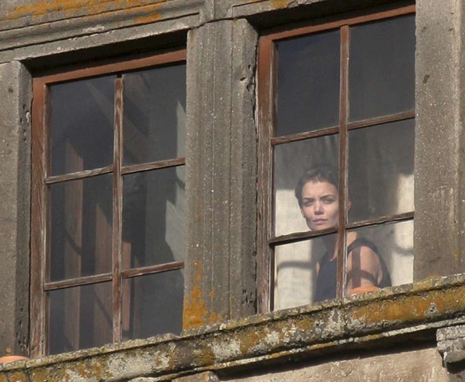 Actress Katie Holmes watches from a window of Castello Odescalchi as her fiance Tom Cruise arrives for their wedding in Bracciano