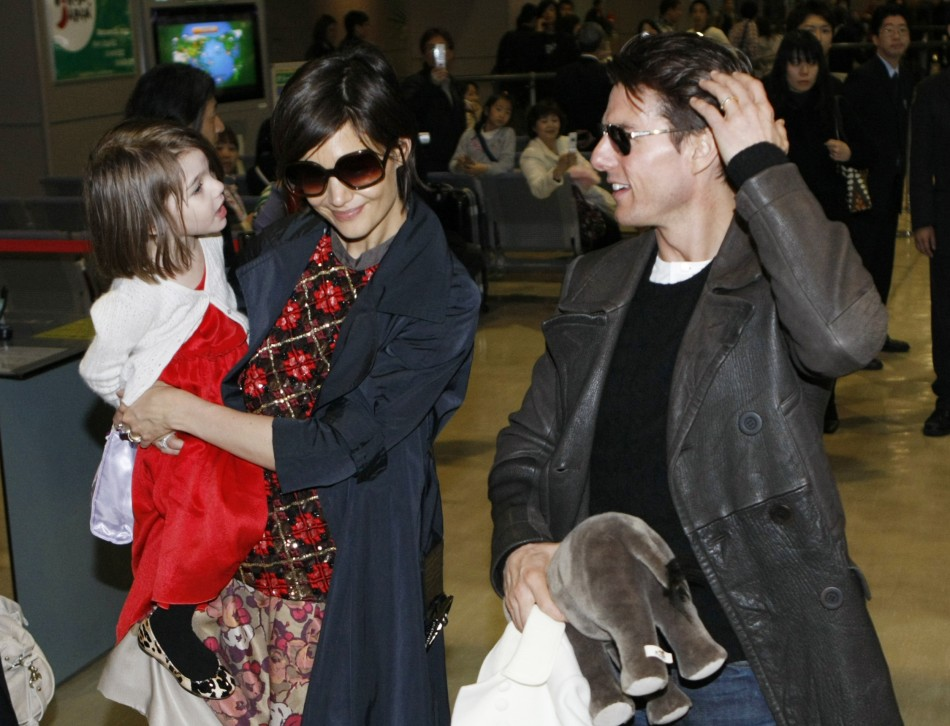 Actor Tom Cruise speaks with his daughter Suri, who is held by her mother Katie Holmes, upon their arrival at Narita international airport in Narita