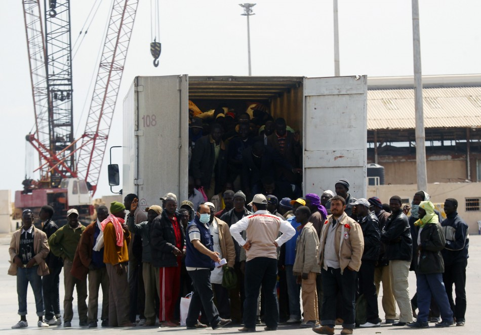 Migrant workers from Africa step out of a truck after arriving in a port in Misrata during an evacuation operation organized by IOM