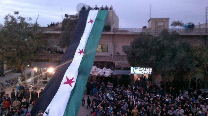 Demonstrators against Syria's President Bashar al-Assad display a large 1961-63 Syrian flag during a march after Friday prayers in Kafranbel near Adlb