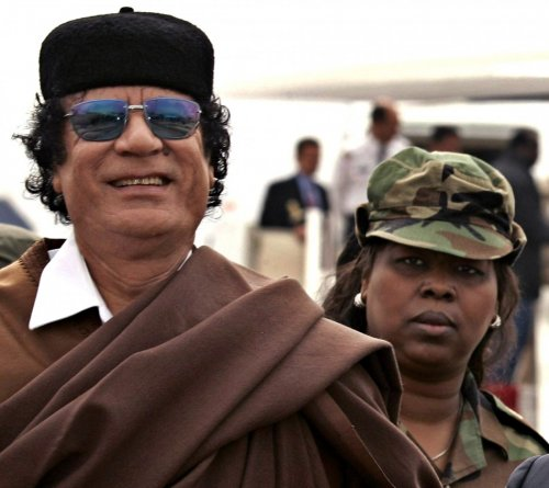 Libyan President Gaddafi is followed by his female bodyguard in Algiers.