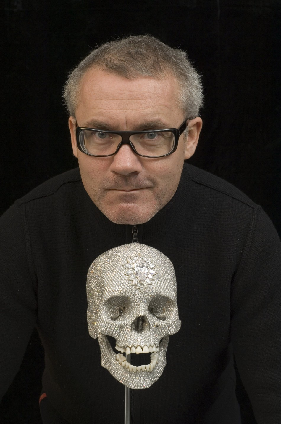 British artist Damien Hirst poses with 'For the love of God'.