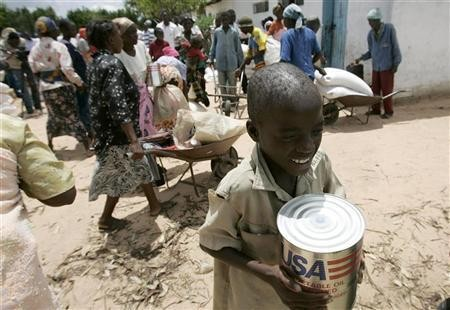 A boy carries a tin of cooking oil from a food aid distribution centre in Chirumanzi