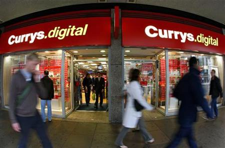 Pedestrians walk past a Currys.digital store in central London