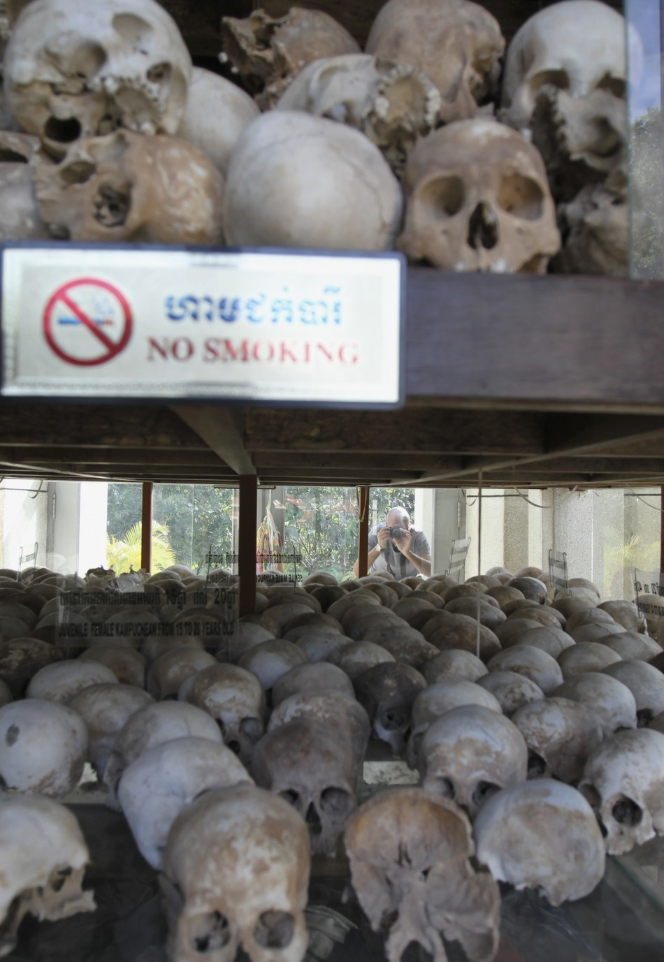 "A tourist takes a photograph of skulls at a memorial stupa at Choeung Ek, a ""Killing Fields"" site located on the outskirts of Phnom Penh"