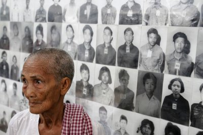 A survivor of the Khmer Rouge regime Hem Sakou stands in front of portraits of victims at the Tuol Sleng S-21 genocide museum in Phnom Penh