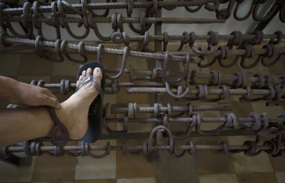 Cambodian man tries on shackles used on prisoners inside the Tuol Sleng Genocide Museum, also known as the notorious quotSecurity Prison 21quot, in Phnom Penh