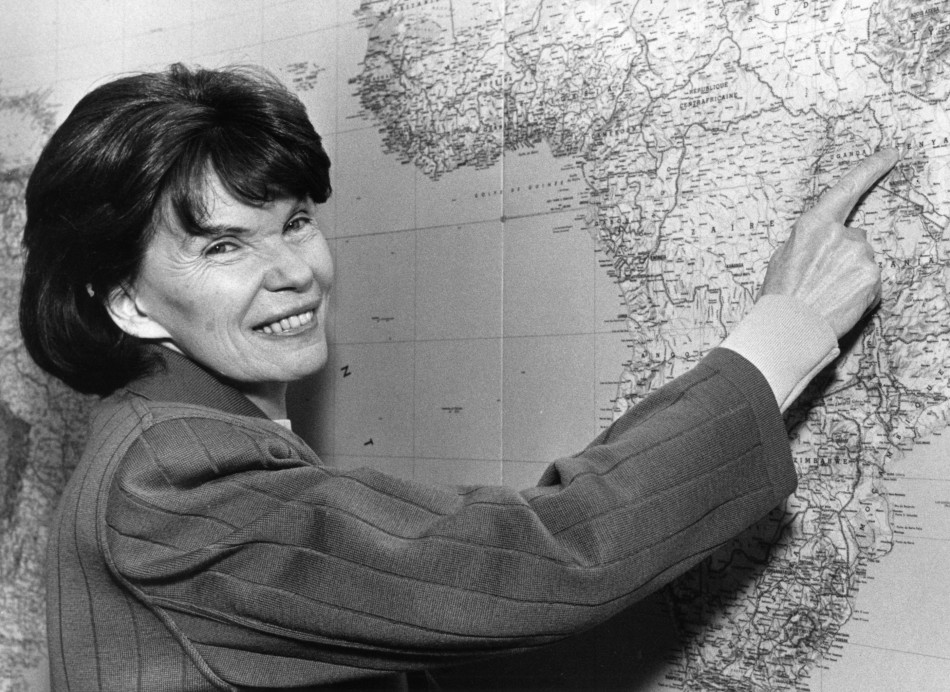 Danielle Mitterrand, the widow of former French President Mitterrand, points to a point in Kenya on a map of the world in her Paris office