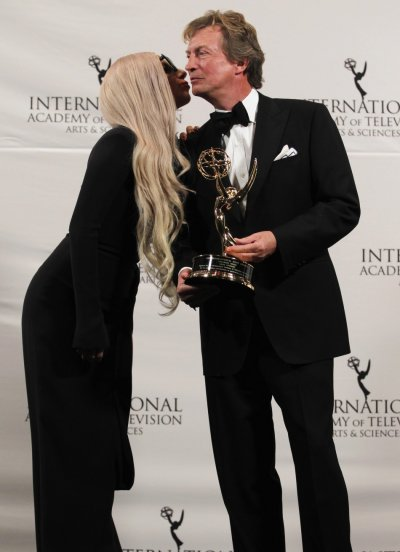Singer Lady Gaga kisses winner of the Founders Award Lythgoe as they pose for a photo at the International Emmy Awards