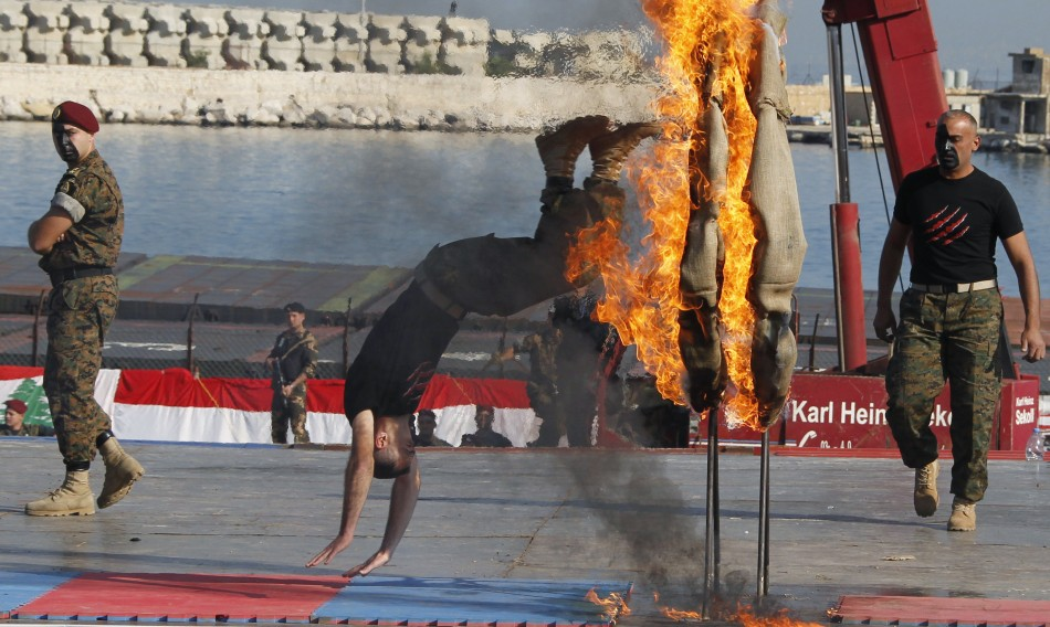 A commando jumps through a flaming hoop during a military parade to celebrate the 68th anniversary of Lebanons independence day in Beirut