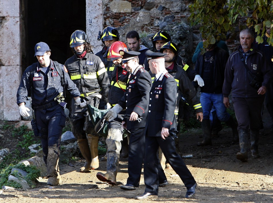 Firefighters and Carabinieri carry the body of a 10-year old boy at Scarcelli, a district of Saponara, in the province of Messina, in Sicily November 23, 2011.