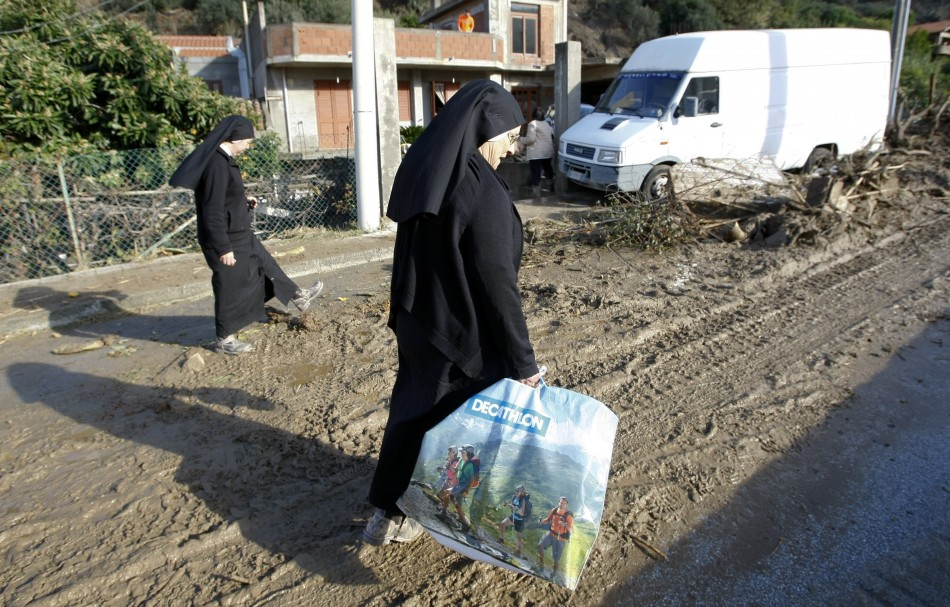 Nuns walk in the mud following a landslide at Scarcelli, a district of Saponara, in the province of Messina, in Sicily November 23, 2011
