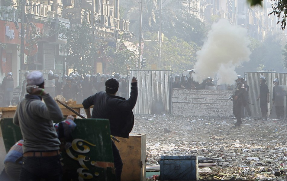Protesters throw stones at police who are firing tear gas, during clashes near Tahrir Square in Cairo