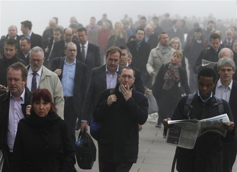 Commuters make their way in the fog across London Bridge towards the financial district of London