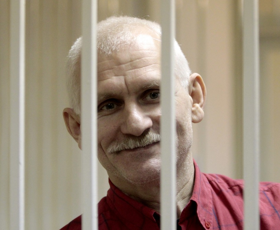 Human rights activist Bialiatski smiles inside a guarded cage in a courtroom in Minsk