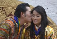 Bhutan's King Jigme Khesar Namgyel Wangchuck (L) kisses Queen Jetsun Pema in front of thousands of residents gathered for the third day of their wedding ceremony at the Changlimithang stadium in Bhutan's capital Thimphu on October 15, 2011.