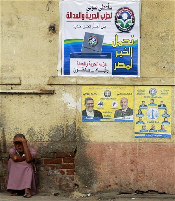 """A beggar sits beside posters for parliamentary elections by Egypt's Muslim Brotherhood """"The Freedom and Justice Party'"""" in Cairo"""