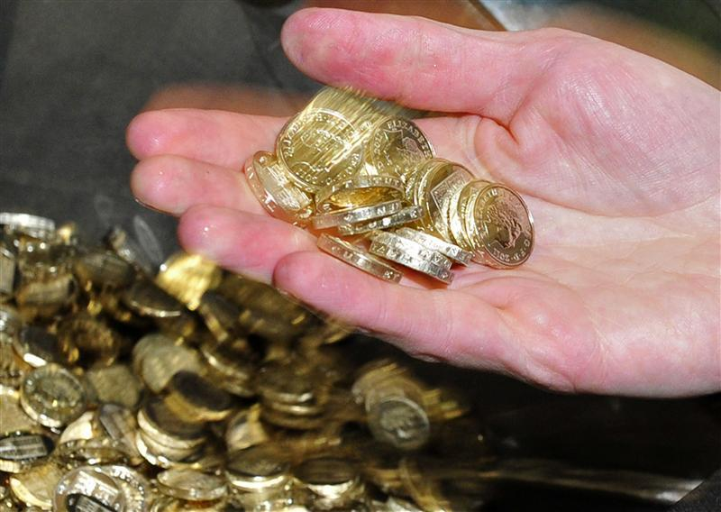Chancellor George Osborne handles newly minted one pound coins during a visit to the Royal Mint in Cardiff