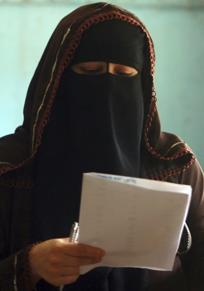 A woman reads her ballot paper before casting her vote at a polling station during the parliamentary election in Cairo