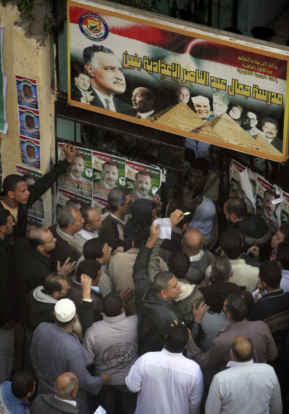 People stand outside a polling station as they wait to cast their votes during parliamentary elections in Cairo